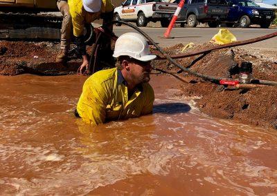 construction worker fixing drainage waist-deep - 2